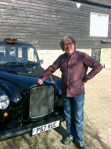 Alan Davies with theTraditional Black Fairway Taxi from London Black Taxis
